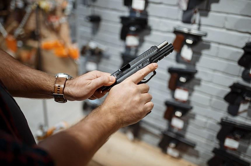 Man Choosing New Handgun In Gun Shop  ------   Homem escolhendo nova arma de mao em loja, revolver. Venda de armas  Foto: Stockphotos