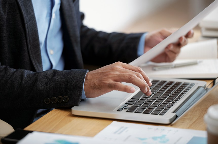 Hands of businessman checking document and typing on keyboard