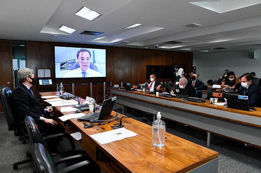 Relator, Veneziano (no telão) defende projeto na reunião da CI desta terça