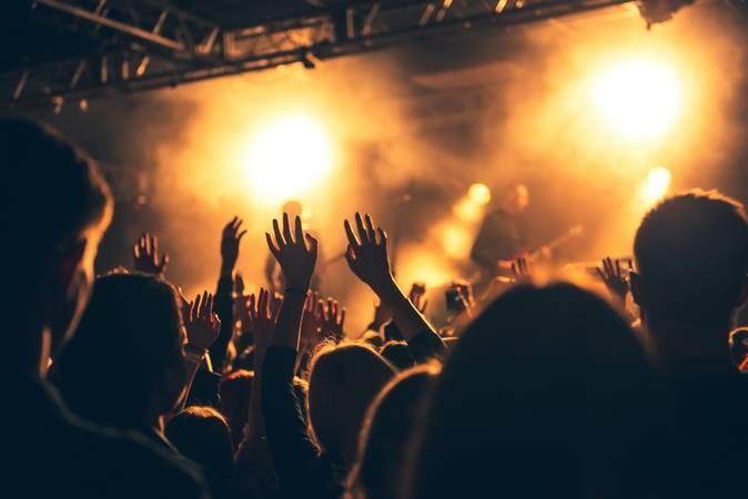 Silhouettes of people in a bright in the pop rock concert in front of the stage. Hands with gesture Horns. That rocks. Party in a club