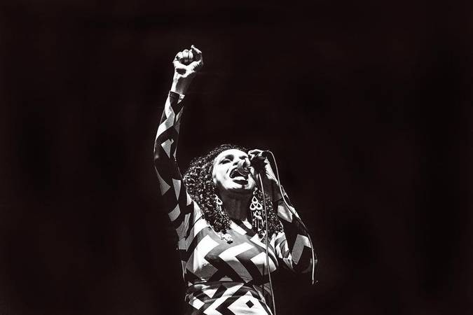 Teresa Cristina cantando com o punho erguido. A foto é em preto e branco.