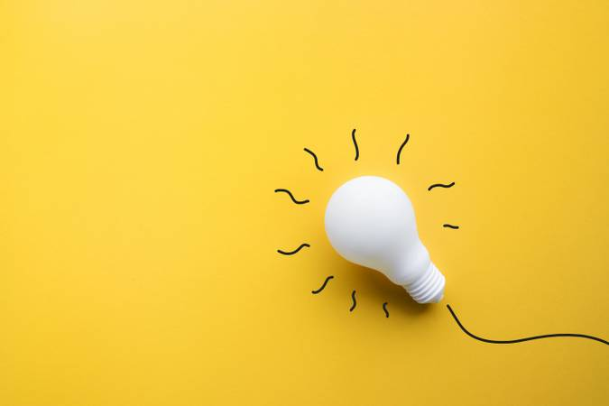 White lightbulb on pastel color background.Ideas creativity,inspiration,concepts.Flat lay design.