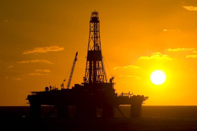 Oil drilling rig in offshore area, during sunset time.  Coast of Brazil, circa 2010.