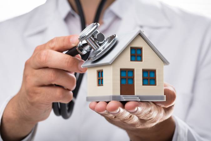 Doctor examining house model with stethoscope