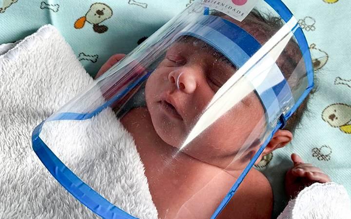 Imagem de recém-nascido com viseira de proteção contra o novo coronavírus.