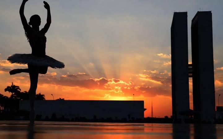 bailarina dançando, na Praça dos Três Poderes, contra a luz do pôr do sol e com as torres do Congresso Nacional ao fundo.