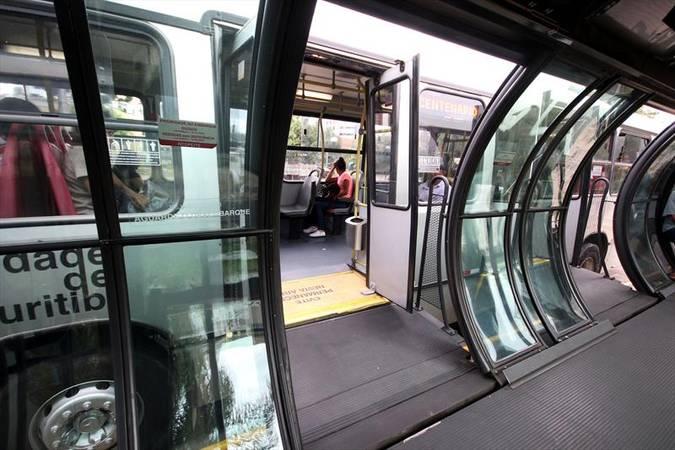 Ônibus urbano de Curitiba parado, com a porta aberta e ligada a uma estação tubo. No fundo da imagem, uma pessoa está sentada em um dos assentos do coletivo.