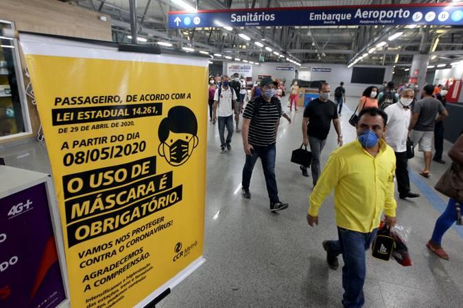 Pessoas em estação de metrô olhando para placa sobre o uso obrigatório de máscaras em vagões do metrô.