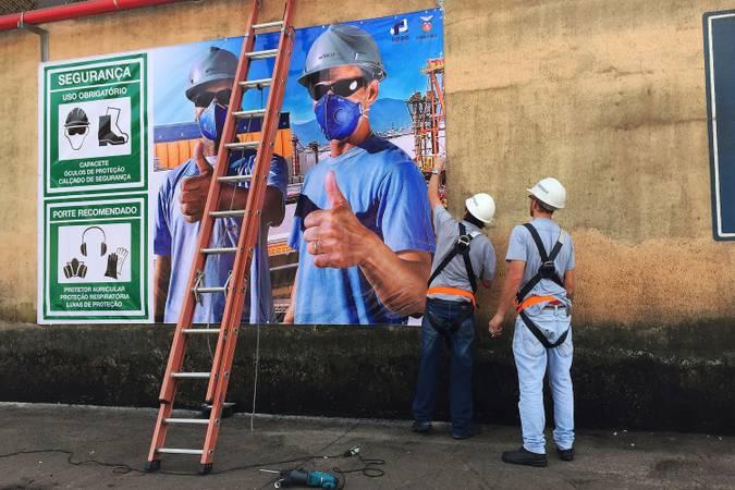Homens colocam em parede banner sobre acidente de trabalho. Na foto do banner, pessoas usam EPIs.
