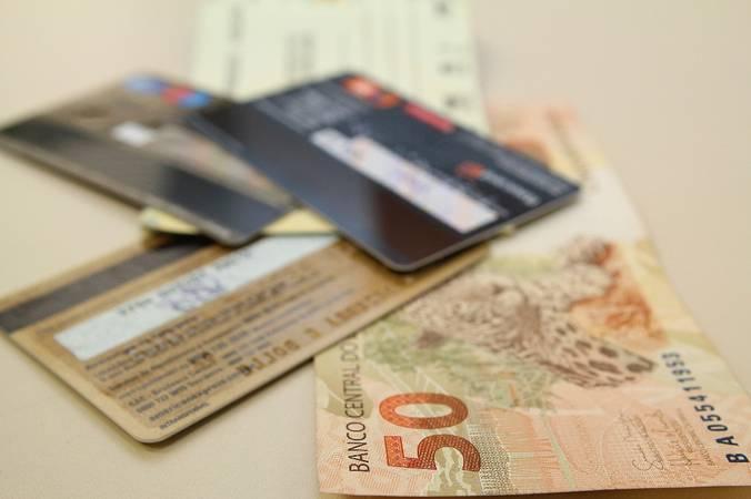 Cartões de crédito e nota de cinquenta reais.