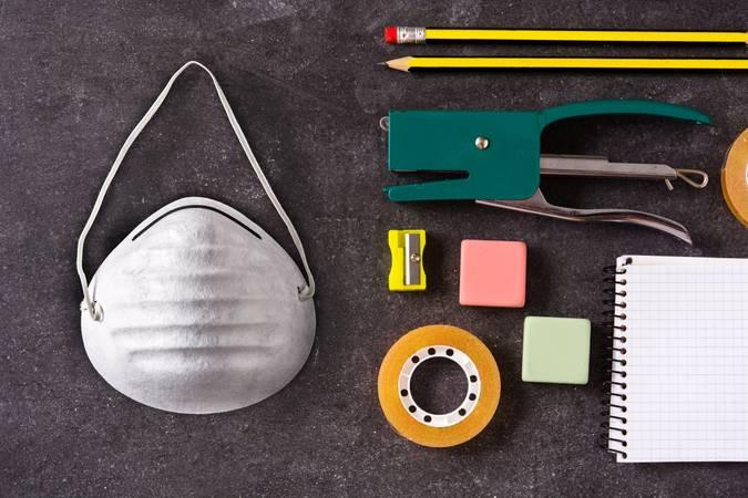 Máscara de proteção ao lado de lápis, durex, grampeador, caderno, apontador e borrachas.