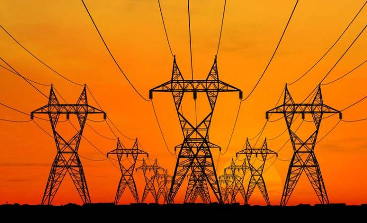 Rede elétrica clicado durante o por do sol. As torres e fiação elétrica, que lembram robôs, contrastando com o horizonte amarelado do por do sol.