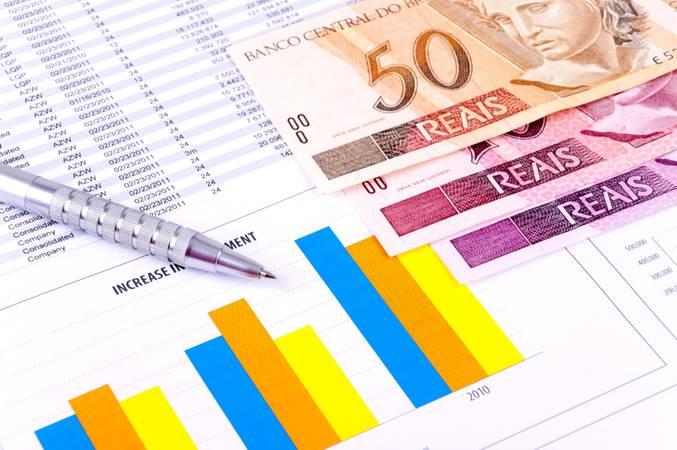 Notas de reais e gráficos financeiros.