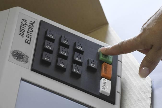Pessoa finalizando voto em urna eletrônica.