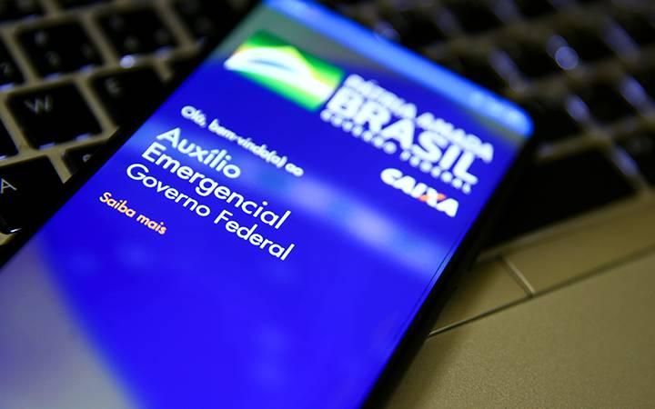 Tela de celular aberta em aplicativo do auxílio emergencial.