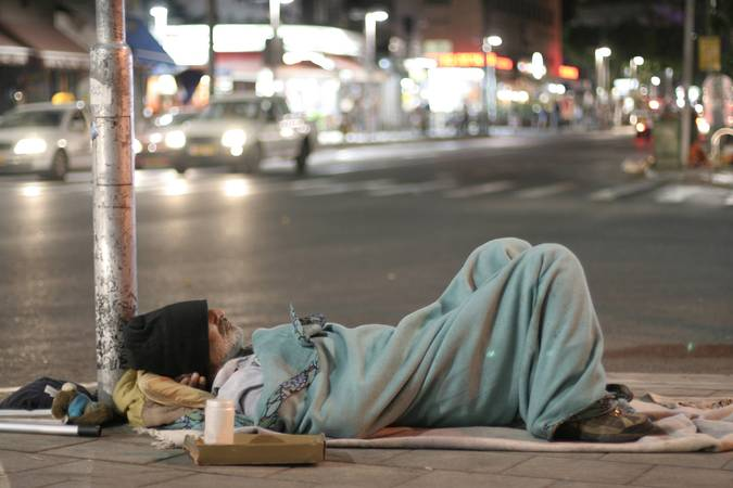 Pessoa em situação de rua dormindo numa esquina.