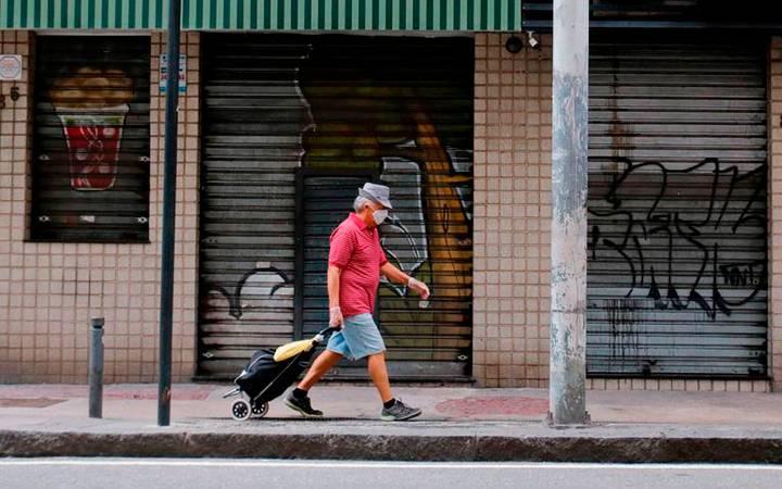 Homem, de máscara, caminha puxando carrinho de feira.