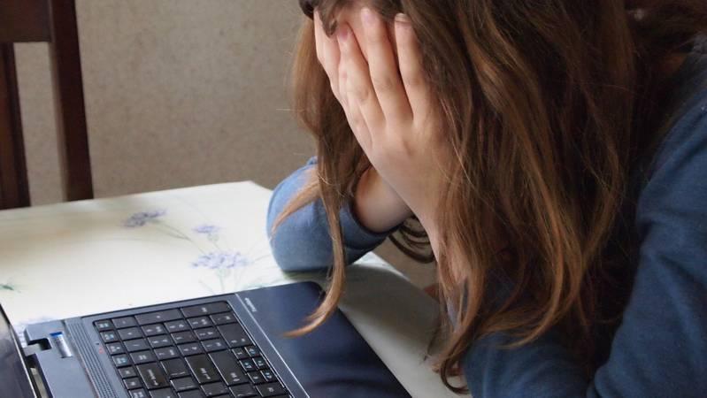 Garota com as mãos no rosto diante de um notebook.