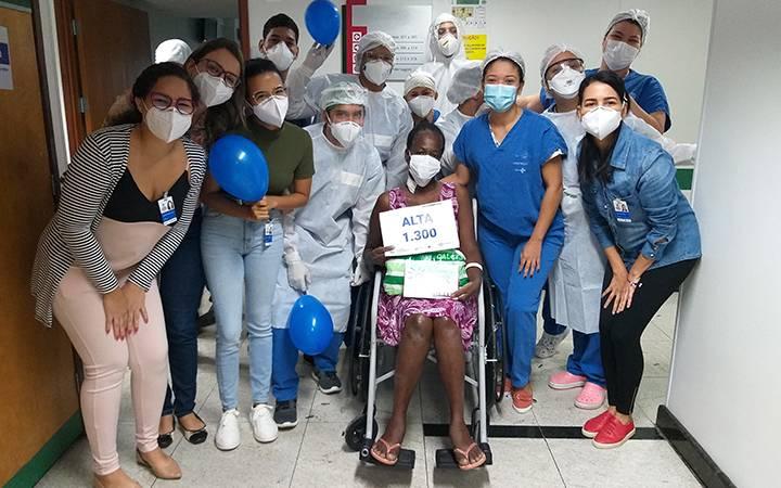 Paciente recebendo alta em hospital referência contra covid-19. A paciente está cercada de profissionais da saúde como médicos e enfermeiros.