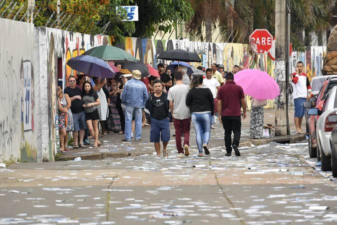 Imagem de arquivo de pessoas na fila pra votar com a rua cheia de santinhos das campanhas eleitorais.