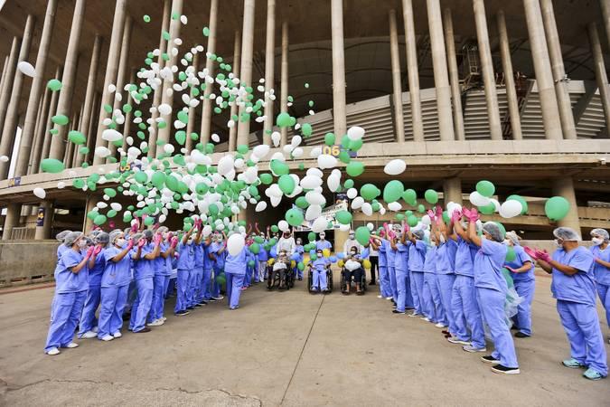 Profissionais de saúde comemorando alta de paciente na porta do Estádio Mané Garrincha, onde foi instalado hospital de campanha para atender pessoas com o novo coronavírus.
