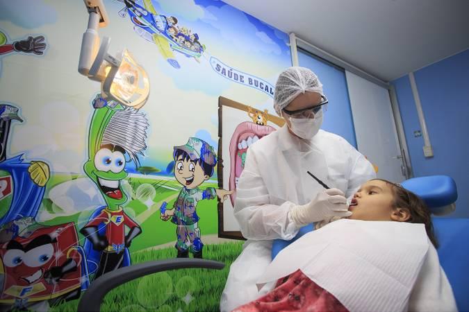 Criança sendo atendida por dentista.