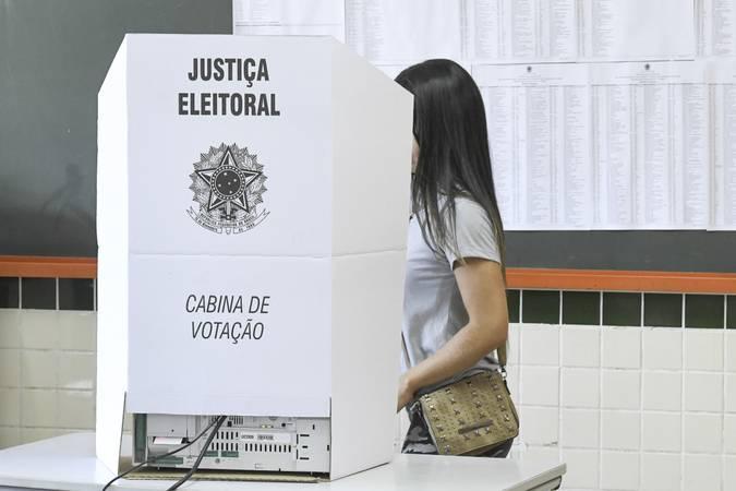 Mulher caminhando em direção a cabine de votação.